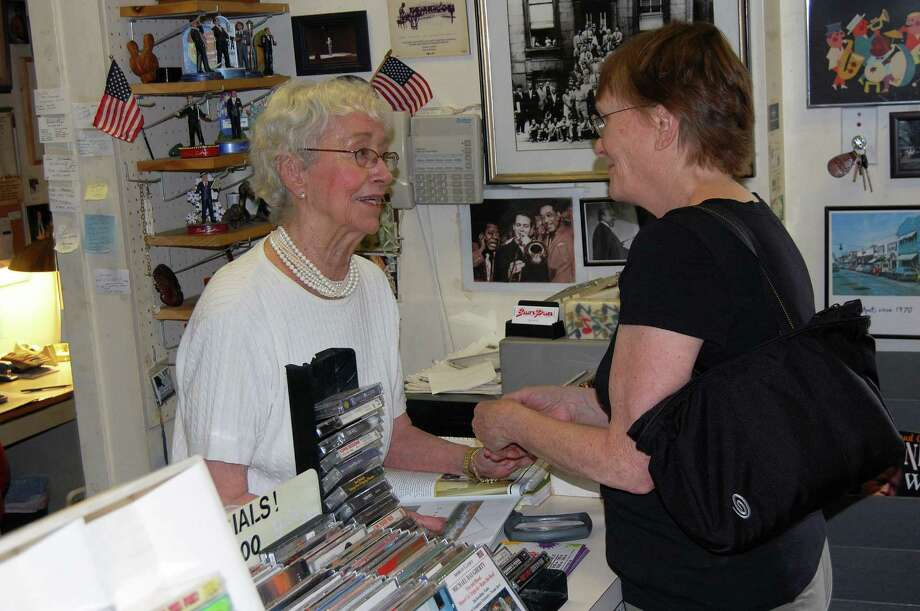 Sally White, left, the longtime owner of Sally's Place music shop in Westport, shakes hands with a longtime patron, Fran White. Sally White said her store is closing at the end of the summer. Sally White has been a mainstay of the downtown record store scene since the 1950s. Photo: Cameron Martin / Westport News