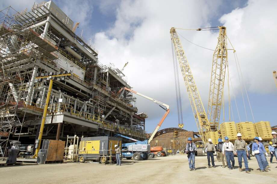 People walk by the topside production module of the Anadarko Petroleum Corporation's Lucius truss spar shown under construction at Kiewit Offshore Services in Ingleside.  ( Melissa Phillip / Houston Chronicle ) Photo: Melissa Phillip, Houston Chronicle