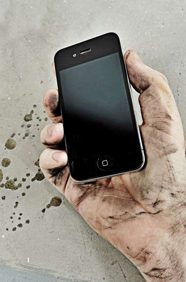 A muddy, oily hand holding an Apple iPhone 4, session for MacFormat Magazine taken on October 5, 2011. Photo: MacFormat Magazine / 2011 Future Publishing Photo by Joseph Branston/MacFormat Magazine via Getty Images