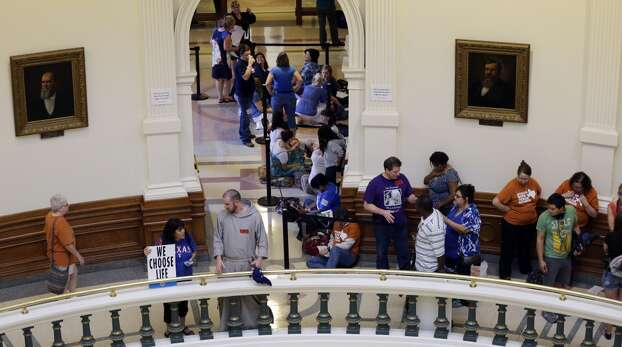 Supporters and opponents of an abortion bill line up outside the Texas Senate chambers as the final vote by the Senate is expected to begin, Friday, July 12, 2013, in Austin, Texas. The bill would require doctors to have admitting privileges at nearby hospitals, only allow abortions in surgical centers, dictate when abortion pills are taken and ban abortions after 20 weeks. (AP Photo/Eric Gay) Photo: Eric Gay, Associated Press