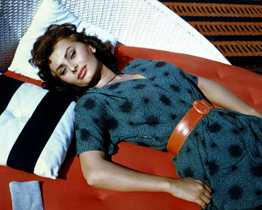 Wearing a blue dress with a red belt, Loren reclines in the sun, circa 1960. (Photo by Silver Screen Collection/Getty Images)