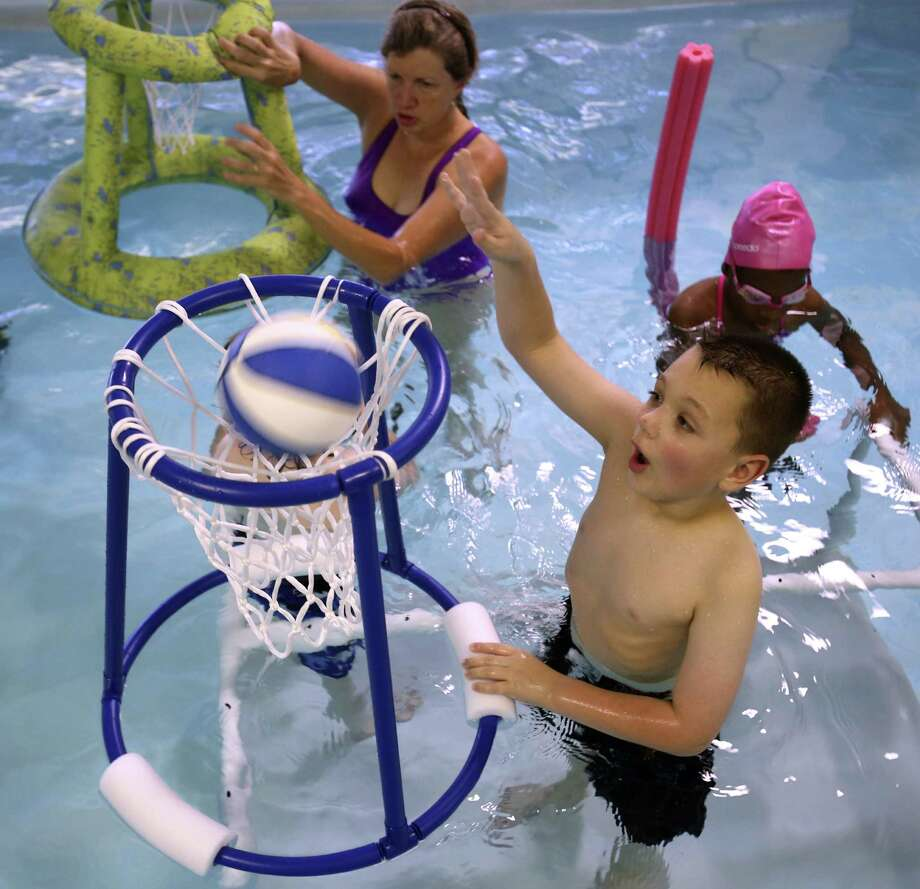 Andrew York (front), 7, plays water basketball during a session with physical therapist Beth McMahon at Stone Oak Therapy. Photo: William Luther / San Antonio Express-News