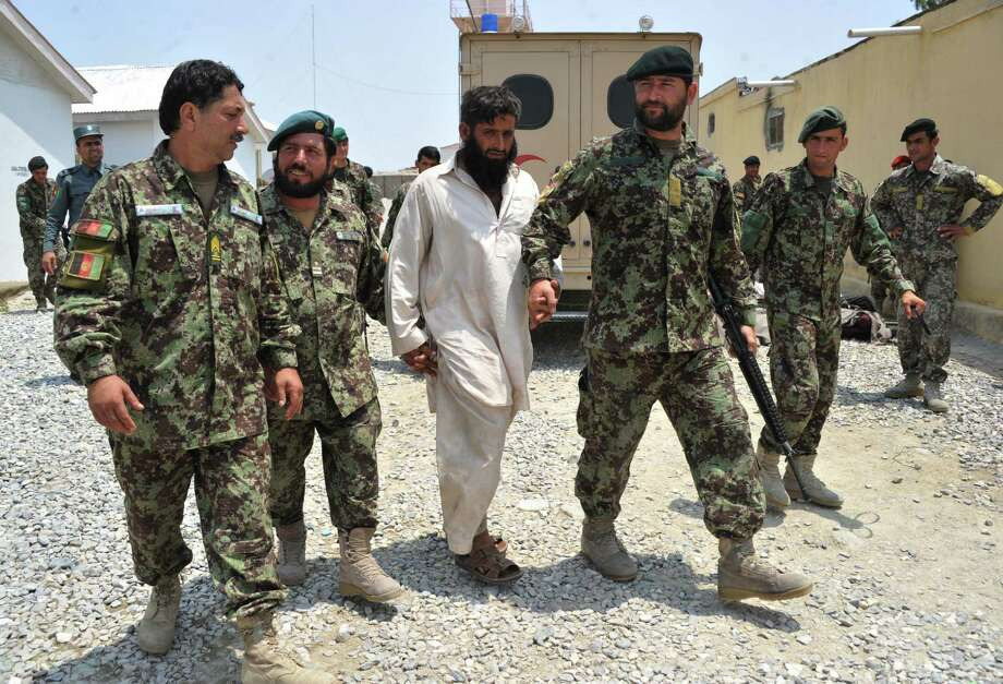 Afghanistan National Army   soldiers walk with an arrested Taliban fighter on  the outskirts of Jalalabad. Afghan  troops are carrying more of the load  but are far from  ready to defend the nation without U.S. help. Photo: Noorullah Shirzada, AFP / Getty Images / AFP