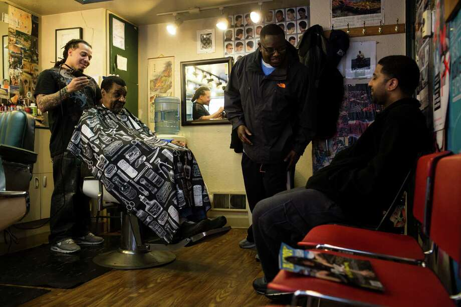 """98104: Including Pioneer Square and much of First Hill, this downtown Seattle ZIP code has become less white in the past decade. From 2000 to 2011, the percent of the population made up by people of color has increased 3.3 points.Above, stylist Devin Mitchell, left, cuts Ed Jones' hair, center left, while """"Country,"""" center, cracks jokes and tells stories with a friend Thursday, March 14, 2013, in the Pioneer Square neighborhood of Seattle. Photo: JORDAN STEAD, SEATTLEPI.COM / SEATTLEPI.COM"""