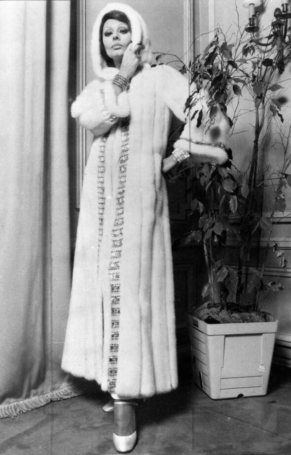 Actress Sophia Loren wearing a hooded white Emba mink coat embroidered with Tyrolean beads.