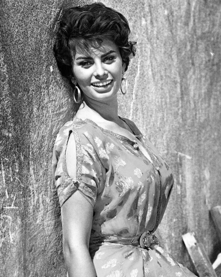 Posing against a wall, wearing a short-sleeve print pattern dress, Loren looks lovely in large hoop earrings, circa 1950. (Photo by Silver Screen Collection/Getty Images)