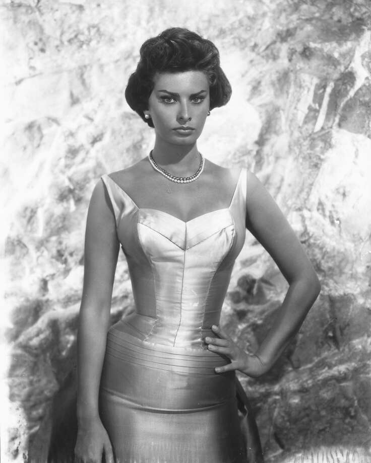 In a sleeveless silk gown and serious expression, Loren poses for a studio portrait, circa 1950.