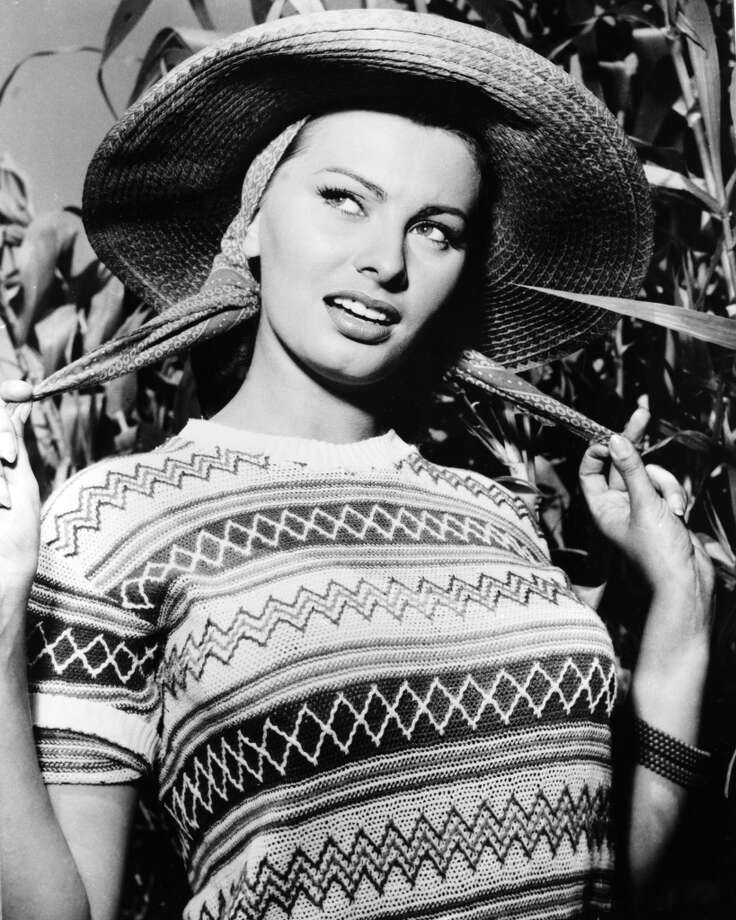 Here she wears a short-sleeve jumper and a wide-brim straw hat, circa 1950.