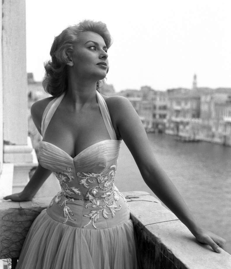 Sophia Loren stands on a terrace on the Canal Grande, wearing a white embroidered dress, Venice, 1955.
