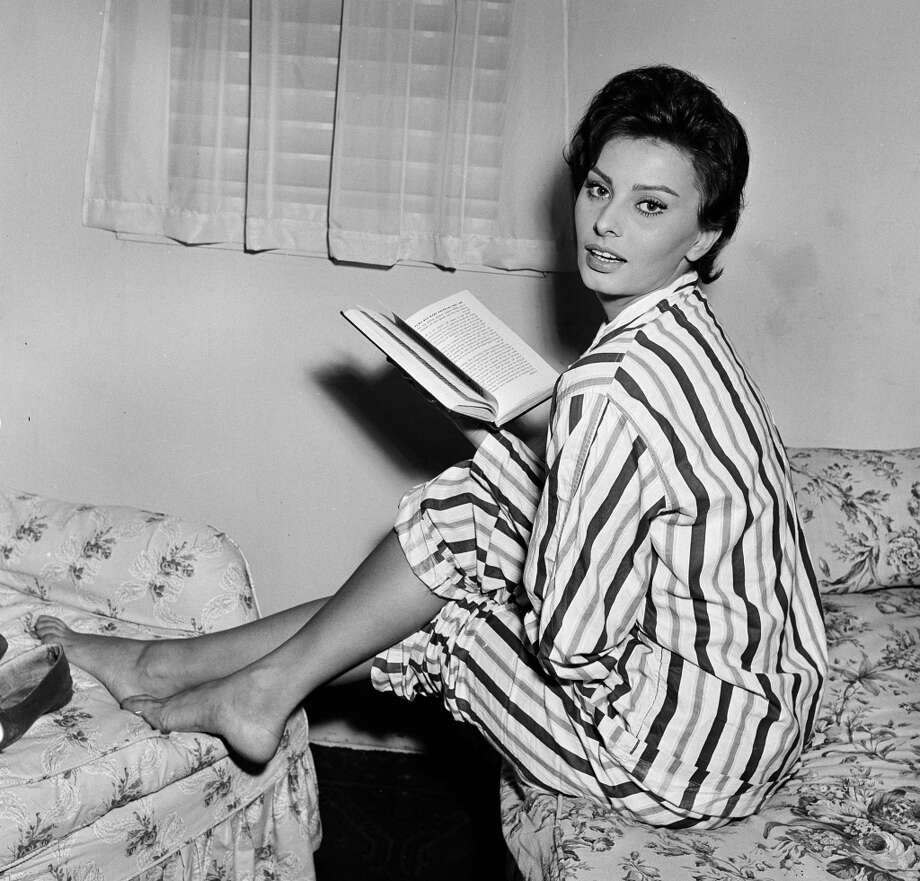 She even makes pajamas look glamorous. Here Loren is reading a book while filming 'The Key' in England, 1957.