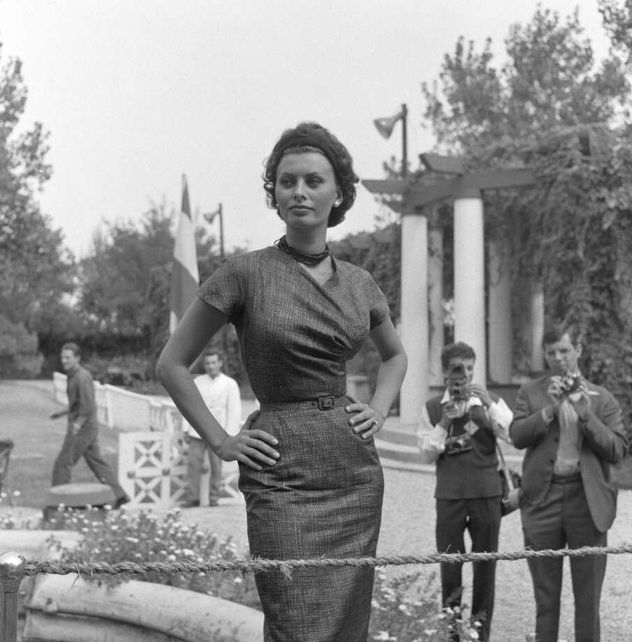 Sophia Loren posing for photographers in a fitted dress in Lido, Venice, 1958.