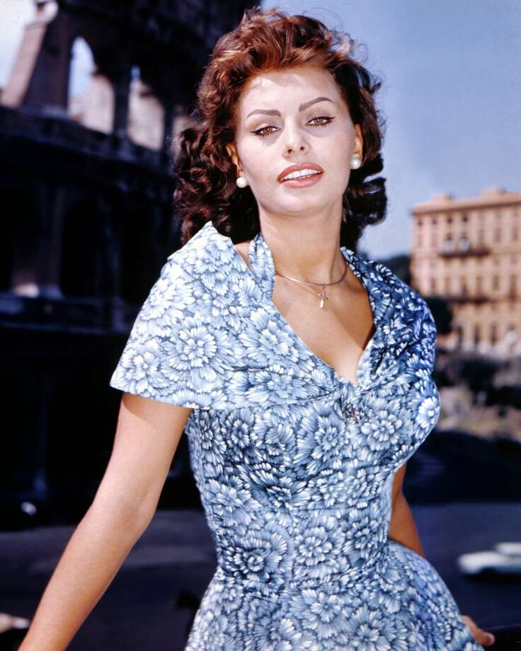 In a short-sleeve, blue and white floral print dress, circa 1960.
