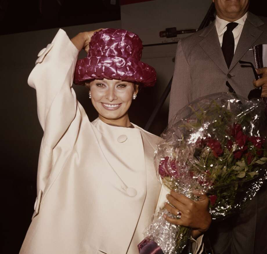 Holding onto her unique pink hat while carrying a bouquet of flowers in London on September 15, 1961.