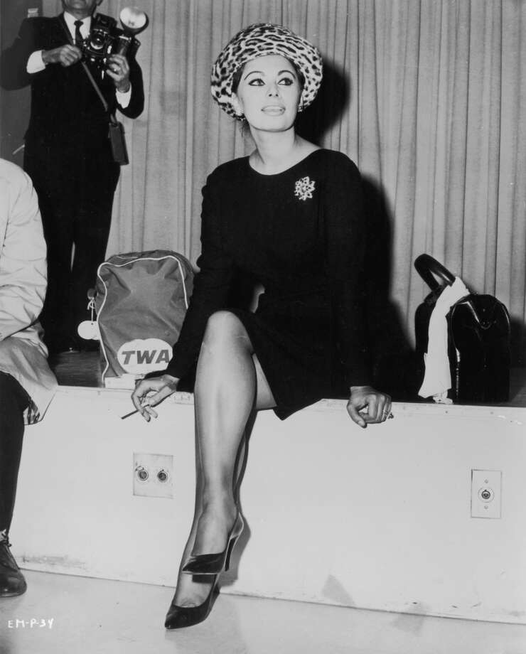 Loren wears a knee-length black dress and leopard print hat while smoking a cigarette in an airport lounge, circa 1965.