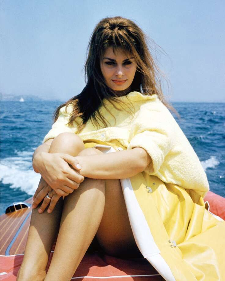 Still looking lovely, even in a yellow raincoat, circa 1965.