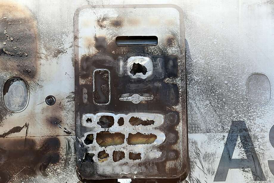 A charred emergency exit door is seen on the wrecked fuselage of Asiana Airlines Flight 214 as it sits in storage at SFO. Photo: Justin Sullivan, Getty Images