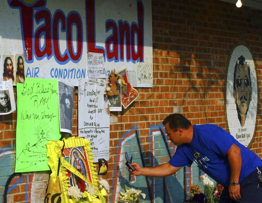 Richard Hodge uses his cell phone to take pictures of a memorial for Ramiro Ayala, the owner of Taco Land who was killed Friday, while at the club Sunday, June 26, 2005.