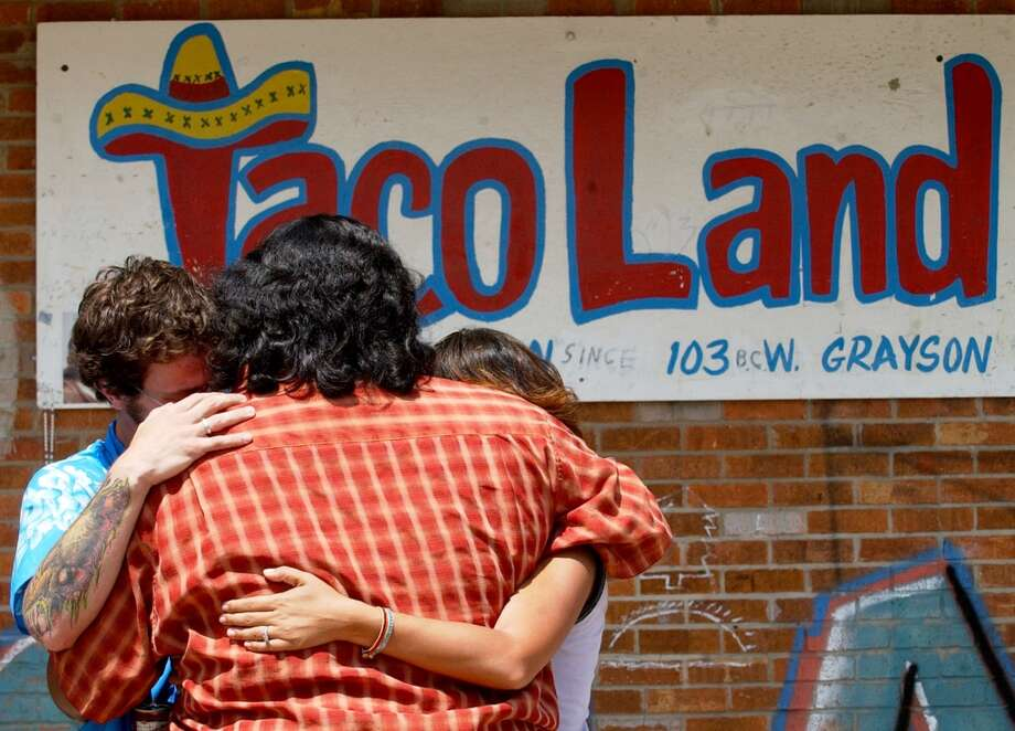 Musician friends of Ramiro Ayala, owner of Taco Land who was killed last night, Cosmo (left) , Marilyn (center, back to camera) and Marie Granato hug outside the club Friday, June 24, 2005.