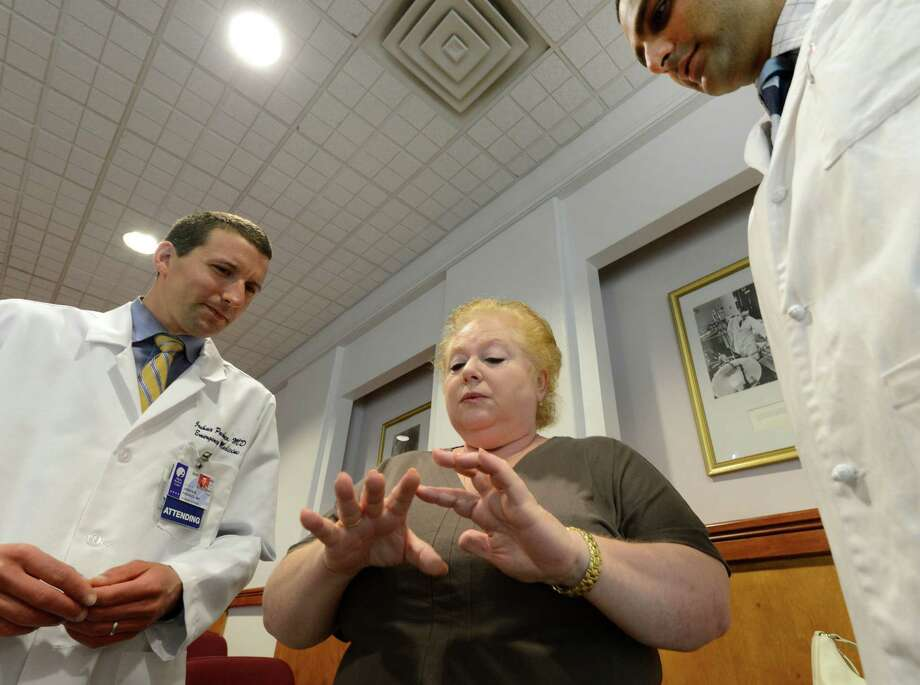 Eleonora Shkaf of East Greenbush shows damage done to her hands after her own dog bit her. Shkaf spoke at a press conference Friday morning, July 12, 2013, at Albany Medical Center in Albany, N.Y., with emergency Room Dr. Joel Pacheco, left and her plastic surgeon, Ashit Patel, right. The purpose of the gathering was to bring attention to the public about the dangers of dogs, whether they are known to you or not.  In the past year more than 200 people have gone to Albany Med's ER for treatment for dog bites. ( Skip Dickstein/Times Union ) Photo: Skip Dickstein / 10023142A
