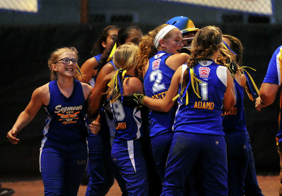 Seymour teammates surround Rebecca Findley who brounght in the winning run to beat North Branford 10-9, during District 1 little league softball championship action in Orange, Conn. on Friday July 12, 2013. Photo: Christian Abraham / Connecticut Post
