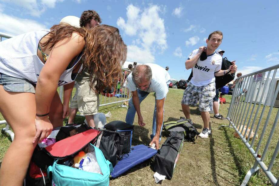 Dennis Nolan with camp security, center, checks bags at the entrance to Camp Bisco Thursday afternoon, July 11, 2013, in Mariaville, N.Y. (Michael P. Farrell/Times Union) Photo: Michael P. Farrell / 00023098A