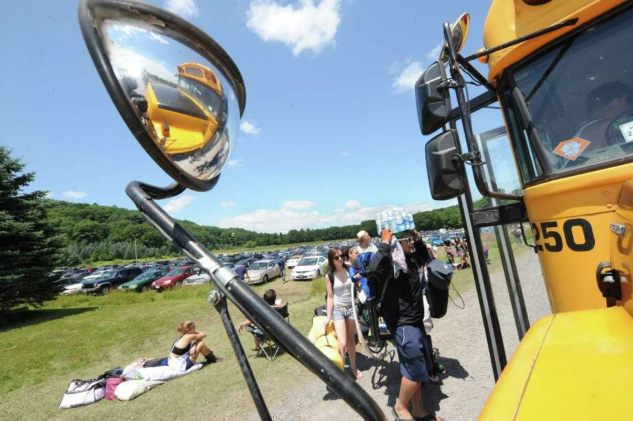 Concert goers board the shuttle bus at Maple Ski Ridge to get to the concert site during Camp Bisco on Thursday July 11, 2013 in Mariaville, N.Y. (Michael P. Farrell/Times Union) Photo: Michael P. Farrell / 00023098A