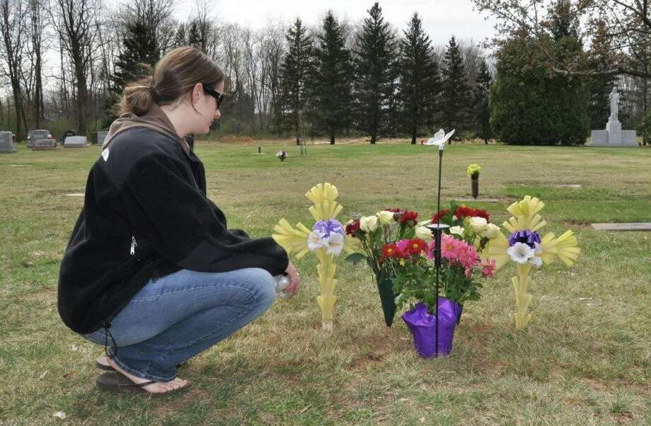 Kaiya Keeler visits a grave. Her mother and grandmother died a day apart in February 2012. In the time since, an anonymous donor has helped finance her classes at Maria College and she hopes to go on to be a nurse like her mother. (Kaiya Keeler / Special to the Times Union)