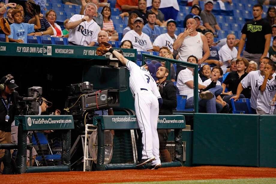 Evan Longoria catches a foul ball near the TV cameras.