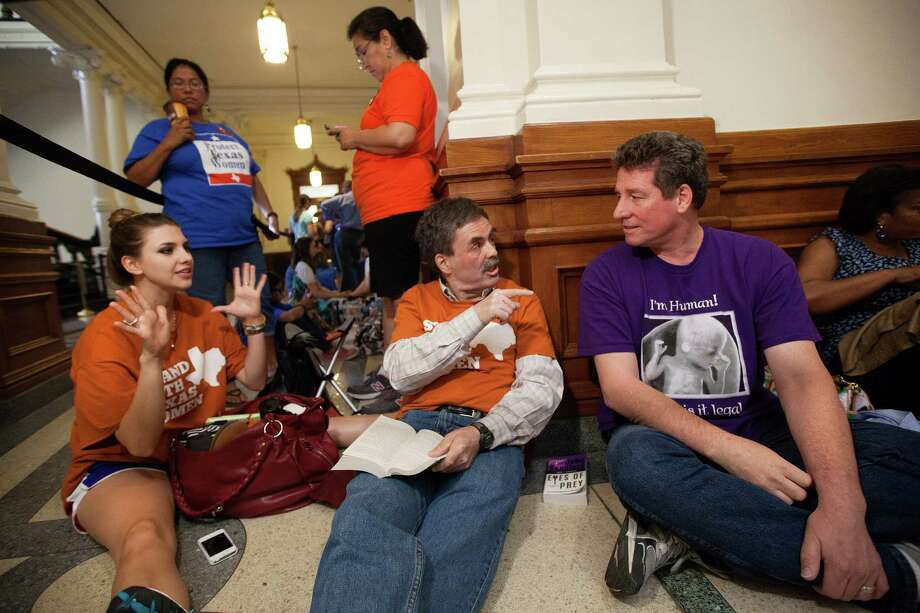 Pro-choice supporters Jessica Nenow, left, and Art Stretton, center, debate abortion rights with Brian McAuliffe, who is against abortions, while waiting in line to enter the Senate gallery at the Texas State Capitol in Austin, Texas, Friday, July 12, 2013. Texas Senate leader, Lt. Gov. David Dewhurst has scheduled a vote for Friday on the same restrictions on when, where and how women may obtain abortions in Texas that failed to become law after a Democratic filibuster and raucous protesters were able to run out the clock on an earlier special session. Photo: Tamir Kalifa, Associated Press / FR170773 AP