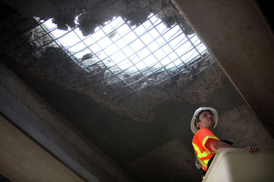 A Texas Department of Transportation employee examines closely the damage to the I-10 westbound overpass in downtown where an 18-wheeler overturned causing major traffic on Friday, July 12, 2013, in Houston. Photo: Mayra Beltran / © 2013 Houston Chronicle