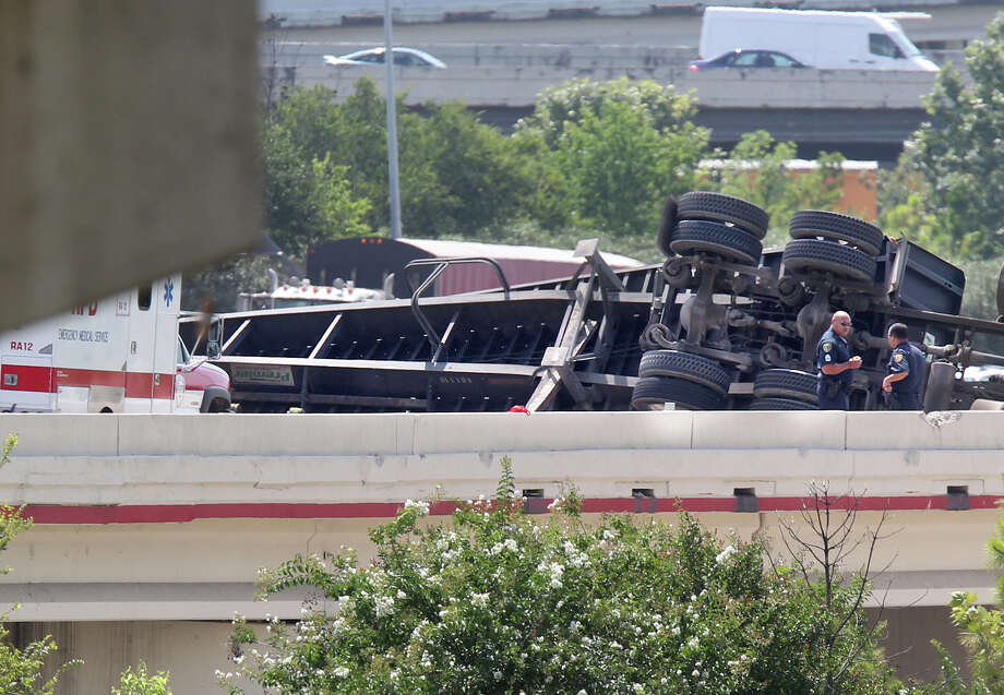 Emergency crews respond to an overturned 18 wheeler  in the westbound lanes of  I-10 in downtown Houston on Friday, July 12, 2013. Photo: Mayra Beltran / © 2013 Houston Chronicle