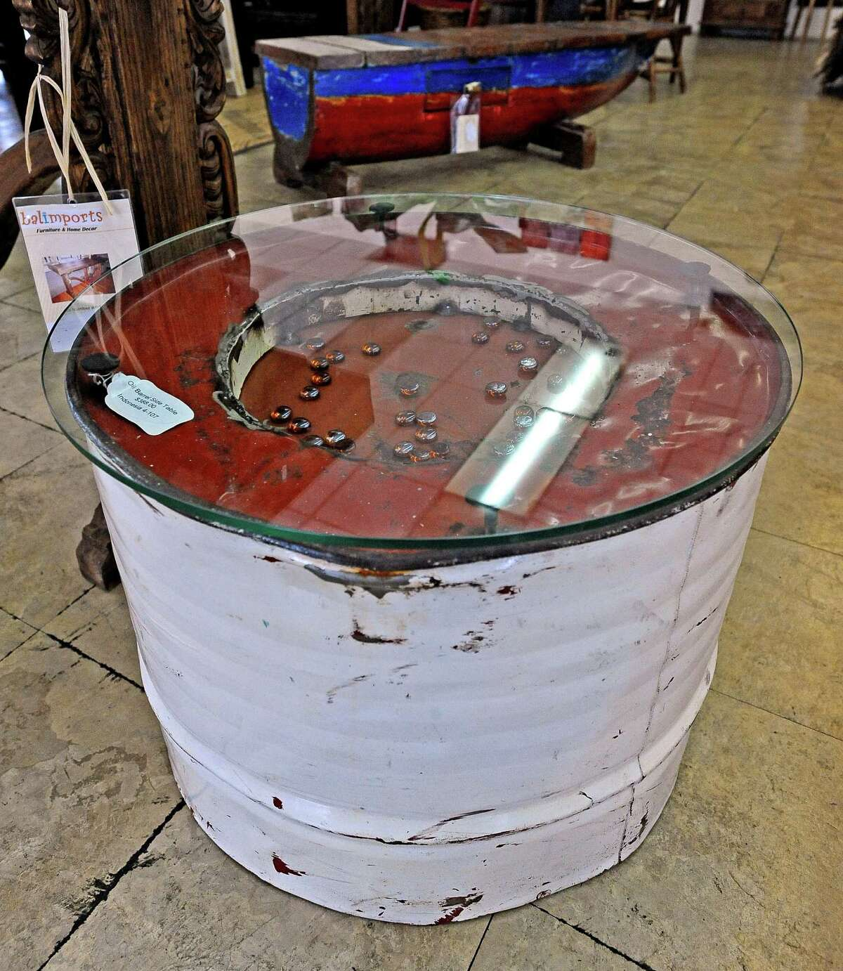Balimports in Beaumont offers a repurposed 55 gallon oil drum that is cut in half and used as a side table with a removable glass top to change internal decor. Photo taken Friday, July 12, 2013. Photo taken: Randy Edwards/The Enterprise