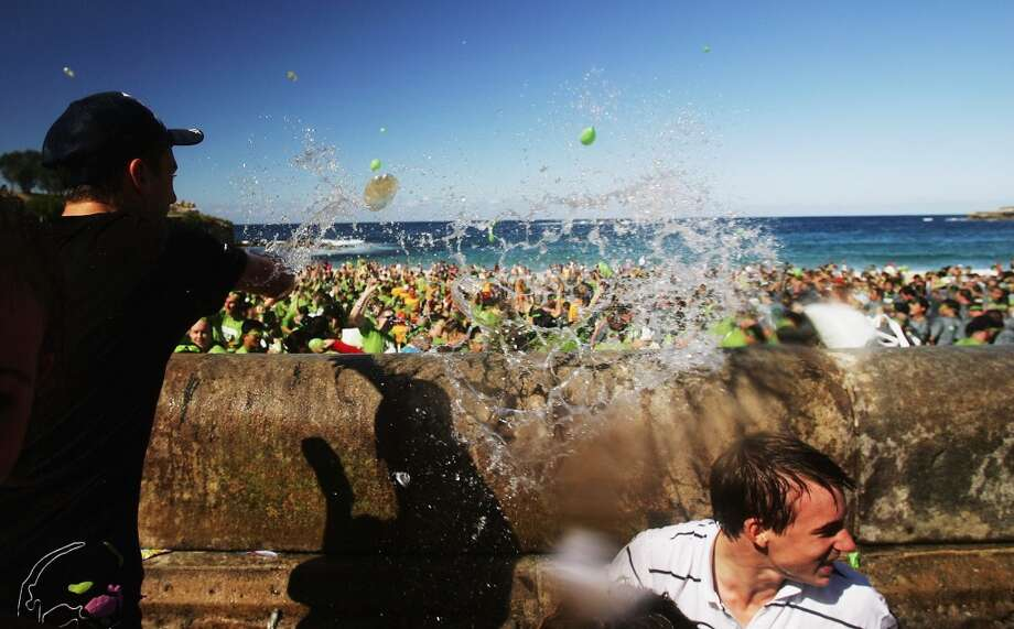 Revelers launch water balloons into the air during an attempt to stage the world's biggest water balloon fight April 22, 2006 in Sydney, Australia. 2921 people threw 55,000 water balloons on Coogee beach to break the record.