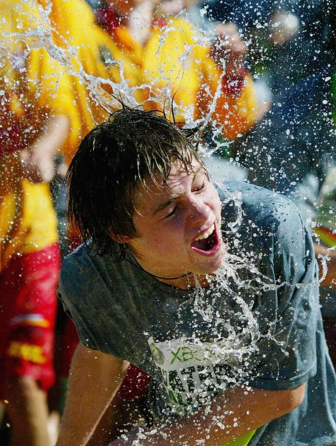 A revelers is hit with a water balloon during an attempt to stage the world's biggest water balloon fight April 22, 2006 in Sydney, Australia. 2921 people threw 55,000 water balloons on Coogee beach to break the record.