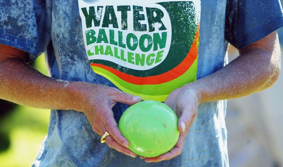 A reveler holds a water balloon during a world record attempt to stage the world's biggest water balloon fight April 22, 2006 in Sydney, Australia. 2921 people threw 55,000 water balloons on Coogee beach to break the record.