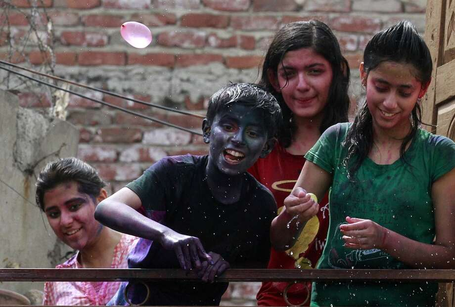 A boy throws a water balloon as children play with colors during the Holi celebration on March 27, 2013 in New Delhi.