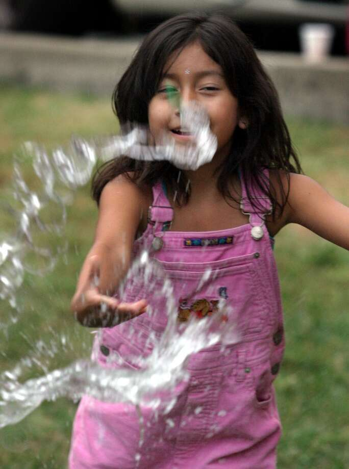 Lisbeth Valencia, 7, has her balloon pop, sending water everywhere, during a water balloon toss game on Aug. 10, 2006 in Arlington, Va.
