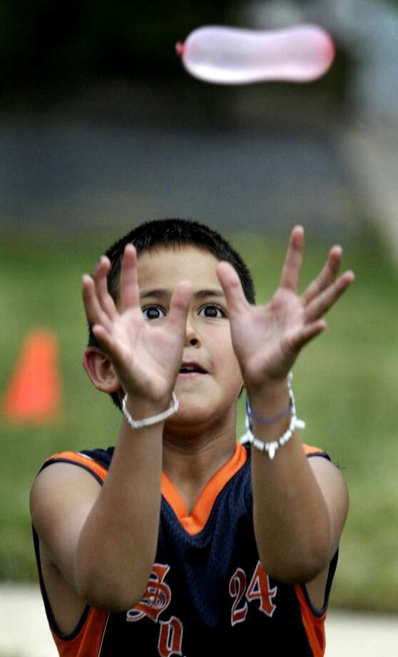 Andres Mendez, 10, concentrates on catching the balloon during a water balloon toss game on Aug. 10, 2006 in Arlington, Va.