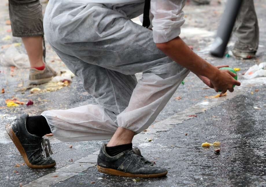 A participant prepares to hurl a water balloon during the annual Vegetable Battle (Gemueseschlacht) on the Oberbaumbruecke on September 2, 2012 in Berlin, Germany. The event pits Kreuzberg district residents againts those of Friedrichshain for control of the Oberbaumbruecke (Oberbaum Bridge), and the two sides pelt each other with rotten vegetables, pet food, ketchup, chicken drumsticks, flour, water guns and styrofoam bats until one side has pushed the other from the bridge. Friedrichshain won the war, in revenge for Kreuzberg's victory the previous year.
