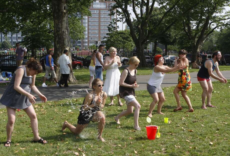 People participate in a water balloon toss as they try and beat the heat at Tom Stofka Garden park June 7, 2008 in the Williamsburg neighborhood of the Brooklyn borough of New York.
