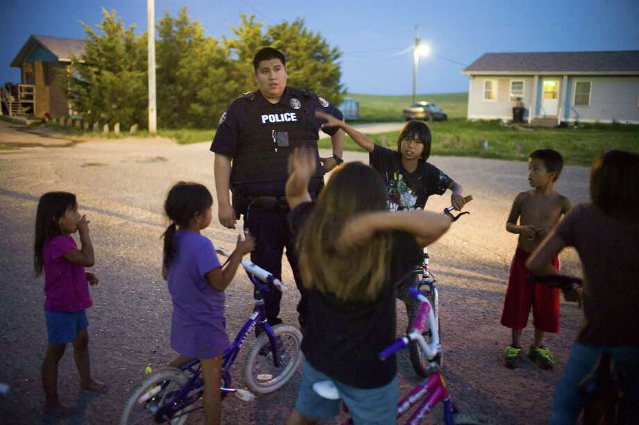 Police officer Tyler Little Finger patrols on foot in the Pine Ridge Indian Reservation in Wounded Knee, S.D., where recent U.S. budget cuts are taking a particularly heavy toll. Photo: Kevin Moloney / New York Times