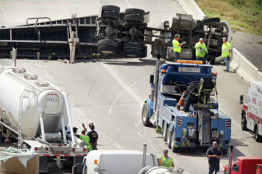 Emergency personnel examine an overturned 18-wheeler that caused major traffic headaches along the westbound lanes of Interstate 10 near downtown on Friday. Photo: Mayra Beltran, Staff / © 2013 Houston Chronicle