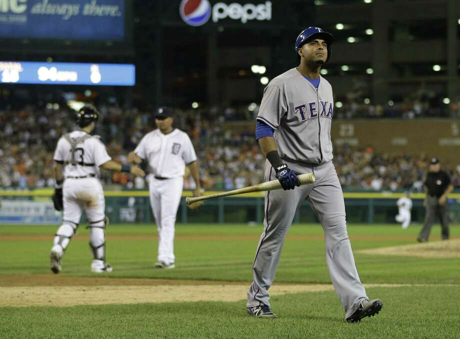 Texas' Nelson Cruz walks back to the dugout after striking out to end the game in an easy Detroit win. Photo: Carlos Osorio / Associated Press