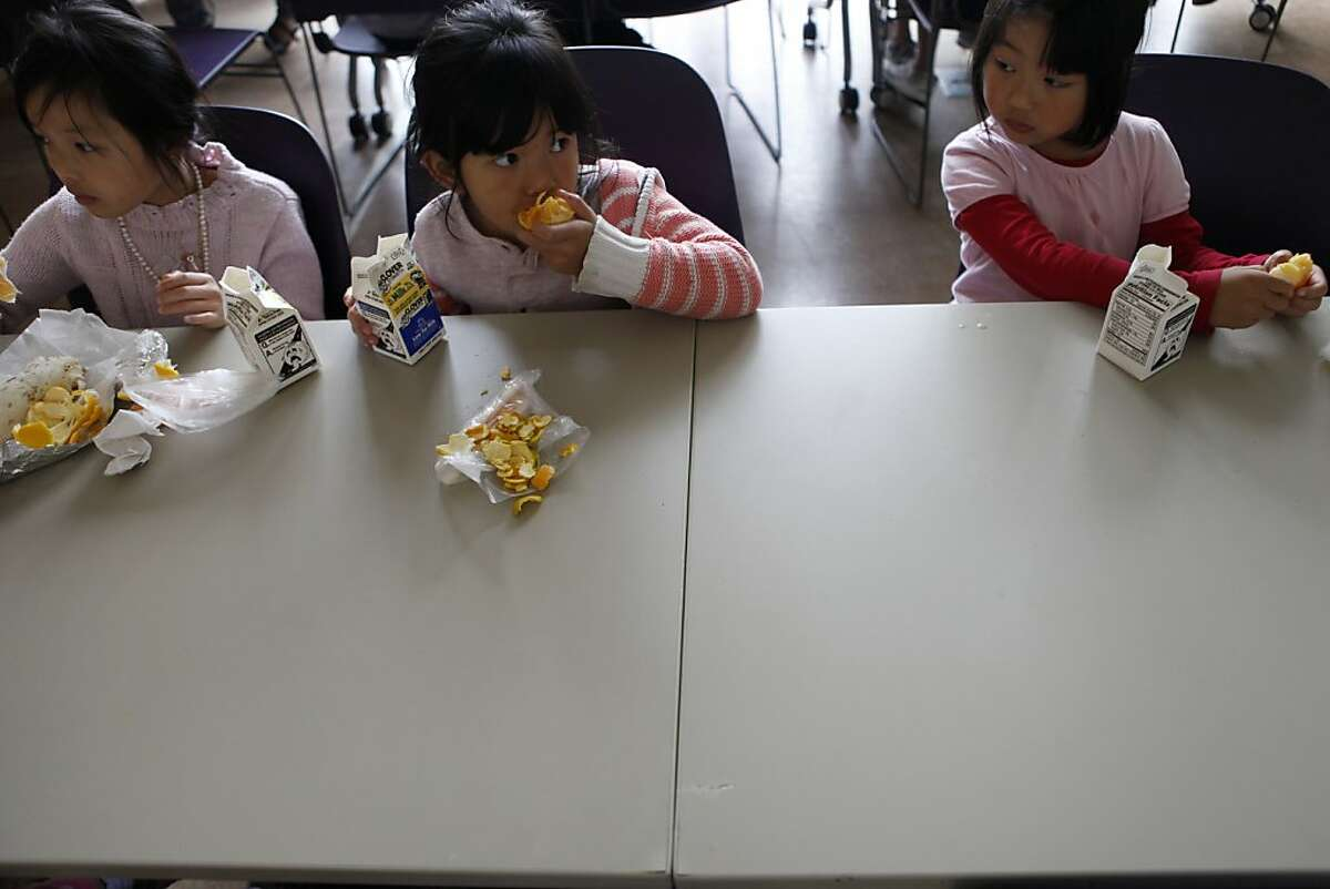 Tiffany Lee, 7, Natasha Deng, 5, and Kevine Liang, 5, eat oranges as part of their free lunch at the Excelsior branch of the San Francisco Public Library on Thursday, July 11, 2013 in San Francisco, Calif. The library serves free lunch for kids and teens this summer, targeted toward students who might be missing out on the free or reduced lunches they get during the school year. On today's date, 29 free lunches were handed out at the library.