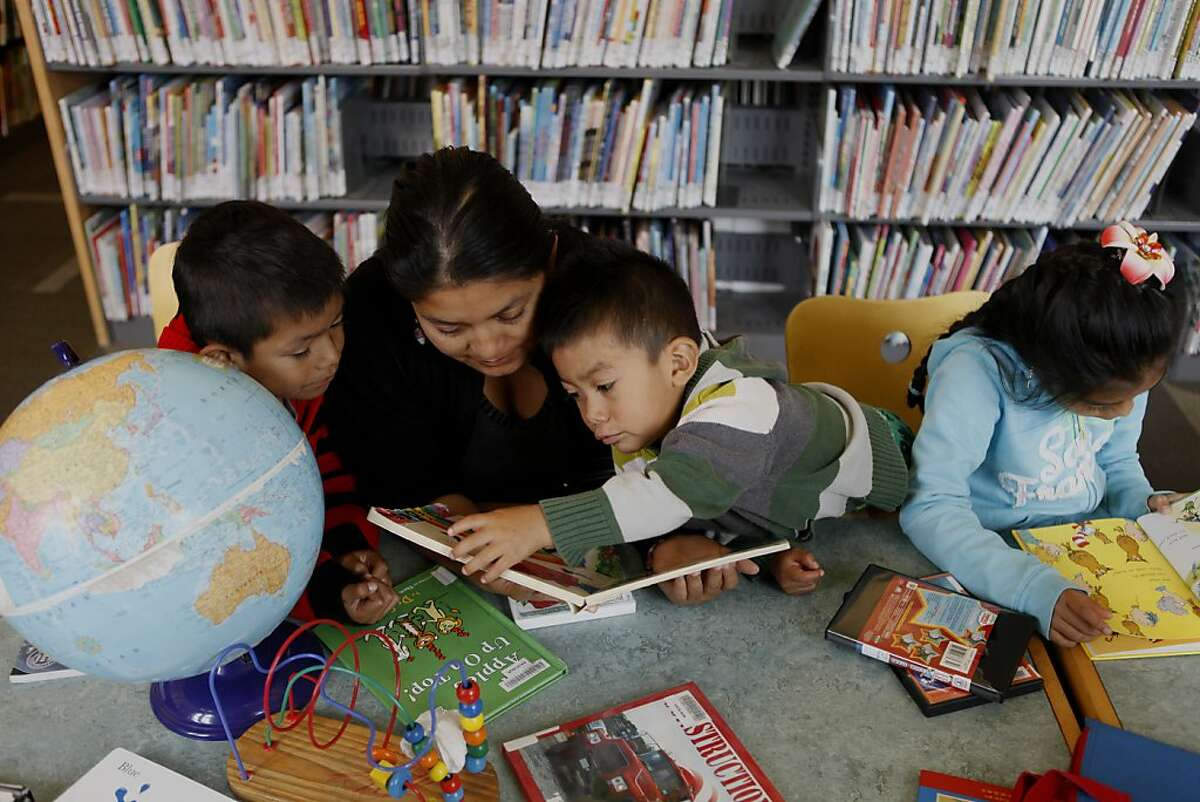 Natalia Velasco reads with her children Darwin Hernandez (left), 6, Mauricio Hernandez ,3, and Adriana Hernandez, 8, after enjoying free lunch at the Excelsior branch of the San Francisco Public Library on Thursday, July 11, 2013 in San Francisco, Calif. The library serves free lunch for kids and teens this summer, targeted toward students who might be missing out on the free or reduced lunches they get during the school year. The hope is that after families have free lunch they will also partake in other resources and activities that library has to offer.