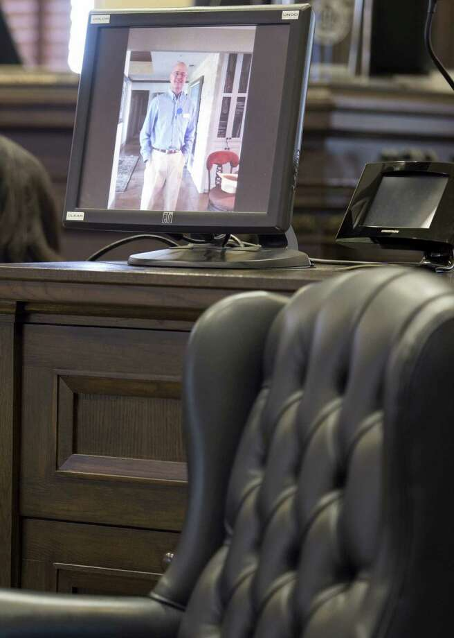A photograph of attorney Ken Nunley is displayed on a computer monitor behind a chair the attorney, who has bladder cancer, was supposed to be sitting at the reception. Photo: Darren Abate / For The San Antonio Express-News