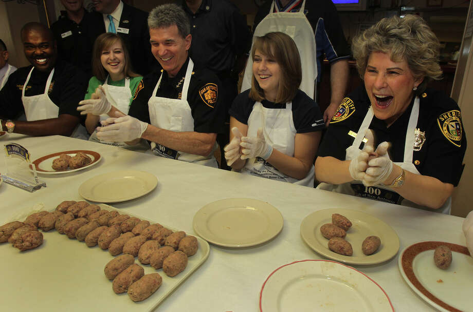 Bexar County Sheriff Susan Pamerleau (right) laughs while making meatballs Friday July 12, 2013 at the Christopher Columbus Italian Society Hall during the 100 Club Annual Meatball Roll in preparation for the upcoming 2013 Annual Spaghetti Dinner to benefit the 100 Club of San Antonio. Along with Sheriff Pamerleau are (from left to right) San Antonio Fire Chief Charles Hood, Miranda Dominguez Morgan, San Antonio Police Chief William McManus, and Michaela Dominguez Morgan. The Dominguez Morgan twins are the daughters of fallen San Antonio police officer Fabian Dominguez who died in the line of duty January 15, 1995. They are both attending Texas Tech University with the help of funds provided by the 100 Club of San Antonio. The spahetti dinner will be held Sunday July 14, 2013 from 11:00 a.m. to 6:00 p.m. . The 100 Club of San Antonio is a non-profit organization which serves the children and families of fallen law enforcement officers and firefighters. Photo: John Davenport, San Antonio Express-News / SAN ANTONIO EXPRESS-NEWS