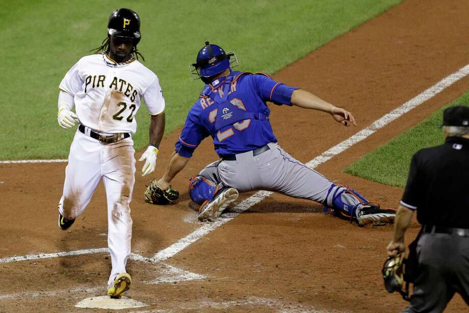 Pittsburgh's Andrew McCutchen, left, had no trouble beating a throw home while scoring the winning run on Friday and leaving Mets catcher Anthony Recker in his wake. Photo: Gene J. Puskar, STF / AP