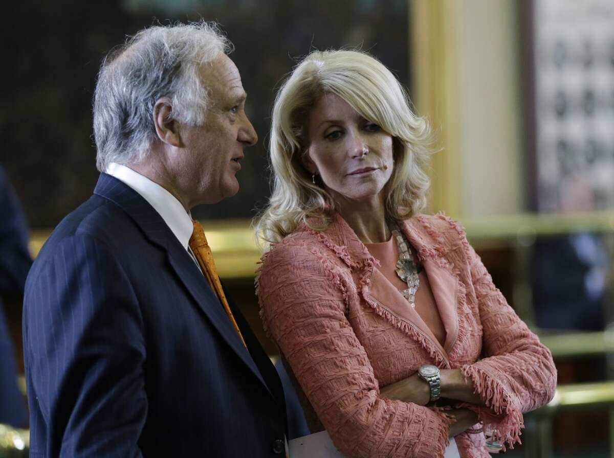 Sen. Kirk Watson, D-Austin, left, and Sen. Wendy Davis, D-FortWorth, right, talk as the Texas Senate debates an abortion bill, Friday, July 12, 2013, in Austin, Texas. The bill would require doctors to have admitting privileges at nearby hospitals, only allow abortions in surgical centers, dictate when abortion pills are taken and ban abortions after 20 weeks. (AP Photo/Eric Gay)
