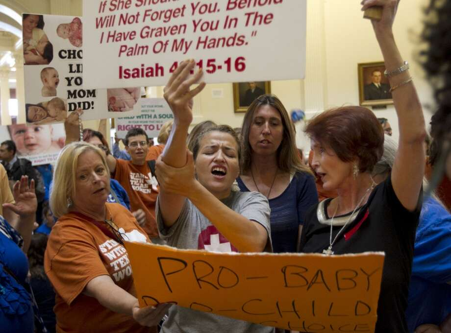Abortion opponent Katherine Aguillar, middle, struggles to keep her sign raised during the debate of the abortion restriction bill,  Friday July 12, 2013  at the Capitol in Austin, Texas  (AP Photo/Austin American-Statesman, Jay Janner)  AUSTIN CHRONICLE OUT, COMMUNITY IMPACT OUT, MAGS OUT; NO SALES; INTERNET AND TV MUST CREDIT PHOTOGRAPHER AND STATESMAN.COM Photo: AP